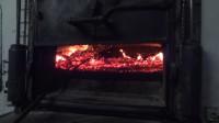 Die Glut wird gleichmässig im Holzofen verteilt, damit sich der Ofen gleichmässig erwärmt.